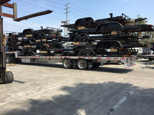 14 Innovative steel open car hauler and utility trailers delivered on a semi, stacked, to Norco Trailers.