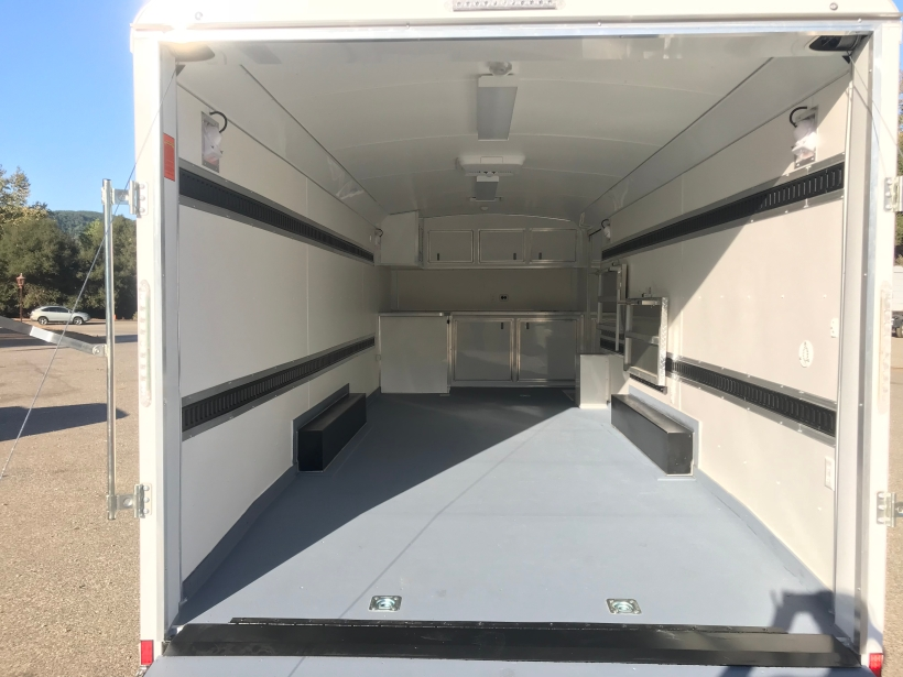 Inside of trailer shows Painted Drymax Floor, White Vinyl Walls,2 rows of E-track running down both sidewalls, Fold down desk and bench, cabinets, A/C, Lights in background.